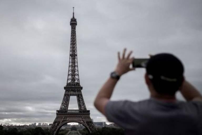Homem de costas fotografa torre Eiffel, central na imagem. O céu está nublado.