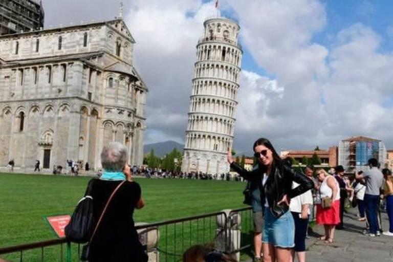 Mulher jovem posa na frente da Torre de Pisa para mulher mais velha fotografá-la.