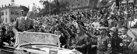 ORG XMIT: 113901_0.tif (FILES) - Picture taken in the year 1937 shows German Chancellor Adolf Hitler (L) standing in a convertible Mercedes reviews SA and SS troops and wellwishers somewhere in Germany. An unnamed Russian billionaire has bought a Mercedes used by Adolf Hitler for several million euros (dollars), a German newspaper report said on November 23, 2009. AFP PHOTO FILES