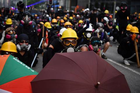 TOPSHOT - Protesters with umbrellas and protective gear face off with riot police at Kowloon Bay in Hong Kong on August 24, 2019, in the latest opposition to a planned extradition law that has since morphed into a wider call for democratic rights in the semi-autonomous city. - Hong Kong riot police on August 24 fired tear gas and baton-charged protesters who retaliated with a barrage of stones, bottles and bamboo poles, as a standoff in a working-class district descended into violence. (Photo by Lillian SUWANRUMPHA / AFP)