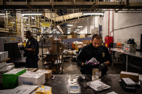 Sustoms and Border Protection officer Mohammed Rahman holds a bag later found to be filled with fentanyl at John F. Kennedy International Airport's mail facility in New York on Sept. 7, 2018. MUST CREDIT: Washington Post photo by Salwan Georges ORG XMIT: 142.0.1202544705