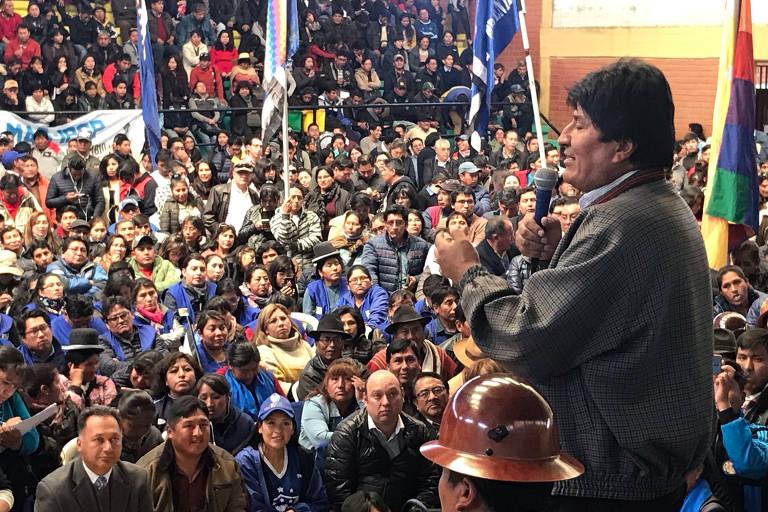 Evo na frente com microfone e multidão ao fundo