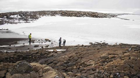 TOPSHOT - People look at the snow at the old glacier after a monument was unveiled at site of Okjokull, Iceland's first glacier lost to climate change in the west of Iceland on August 18, 2019. (Photo by Jeremie RICHARD / AFP)