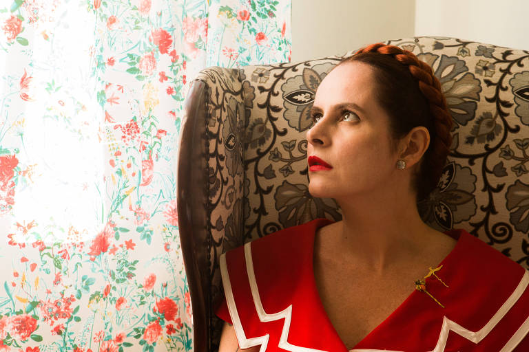 Fernanda Young sentada em uma poltrona olhando para o alto usando um vestido vermelho com listras brancas