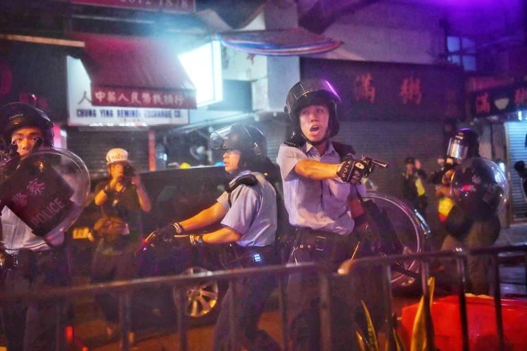 Policiais aponta arma para manifestantes em Hong Kong