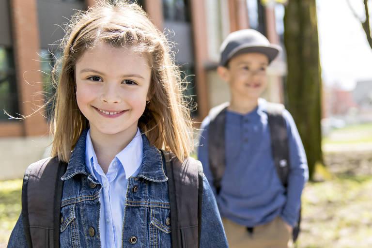 Dois estudantes de sete anos; uma menina loira à frente e um menino de boina atrás