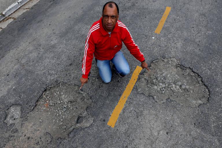 O aposentado Sergio Marques da Silva Souza Tito, 40 anos, afirma que faixas de trânsito foram repintadas antes de buracos serem tapados; ele explica que via é passagem para veículos de transporte público
