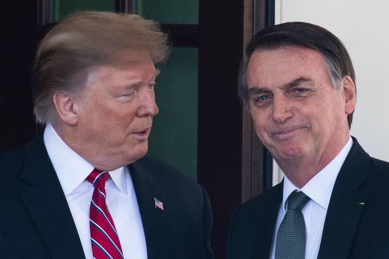 Na foto, Trump fala algo para Bolsonaro, que sorri