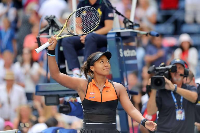 Naomi Osaka ergue a raquete para saudar o público