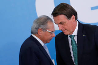 Brazil's President Jair Bolsonaro reacts near Brazil's Economy Minister Paulo Guedes during the ceremony to launch the new worker fund stimulus at the Planalto Palace in Brasilia