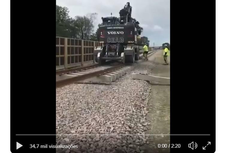 Vídeo mostra linha de trem em construção por máquina da marca volvo e com as inscrições Ceab. Dia nublado e vegetação no entorno é de árvores de clima frio. há funcionários trabalhando com calça e casacos