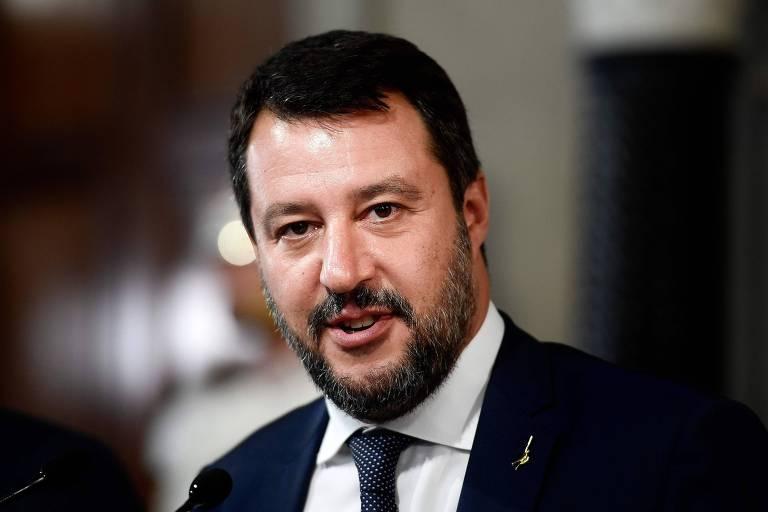 O político italiano está de terno e gravata sorrindo para a foto