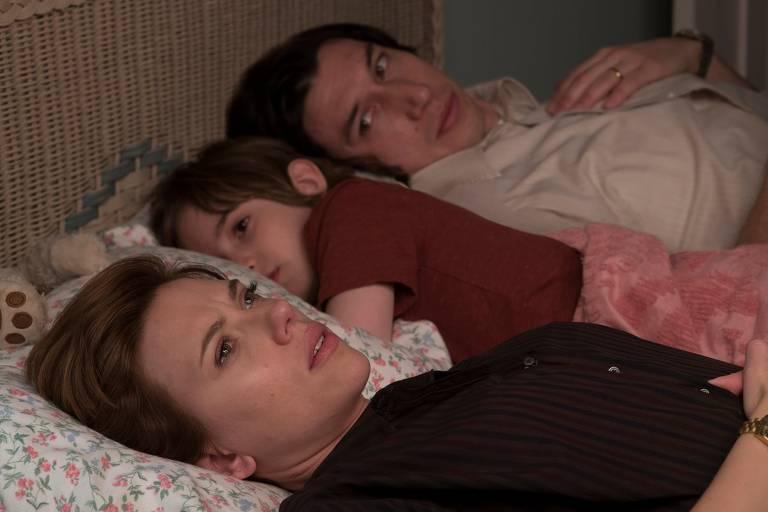 uma mulher e um homem deitados na cama com sua filha pequena no meio