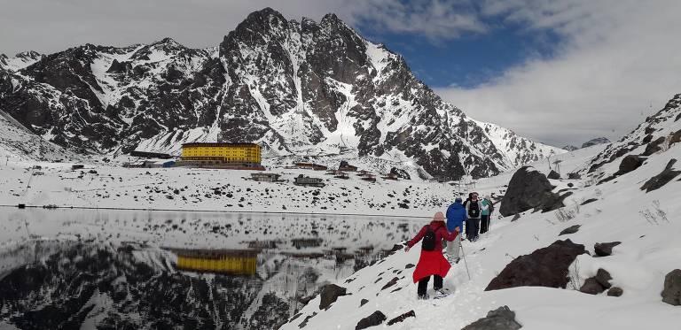 Pessoas caminhando em montanha com neve