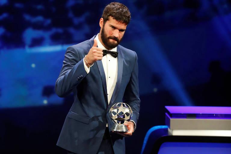 Alisson faz sinal de positivo ao receber o troféu de melhor goleiro da temporada
