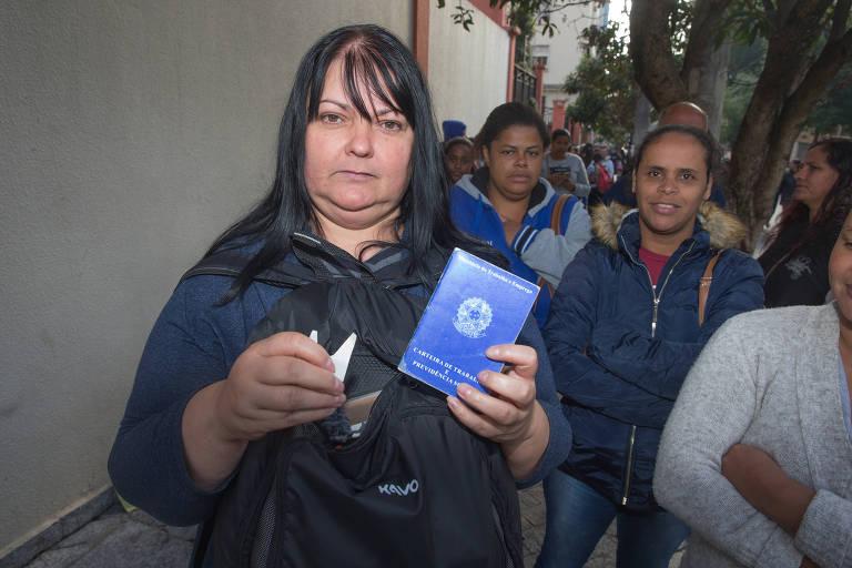 Mulher branca, de cabelo liso, com mochila, segura carteira de trabalho na mão esquerda e papel com senha na mão direita