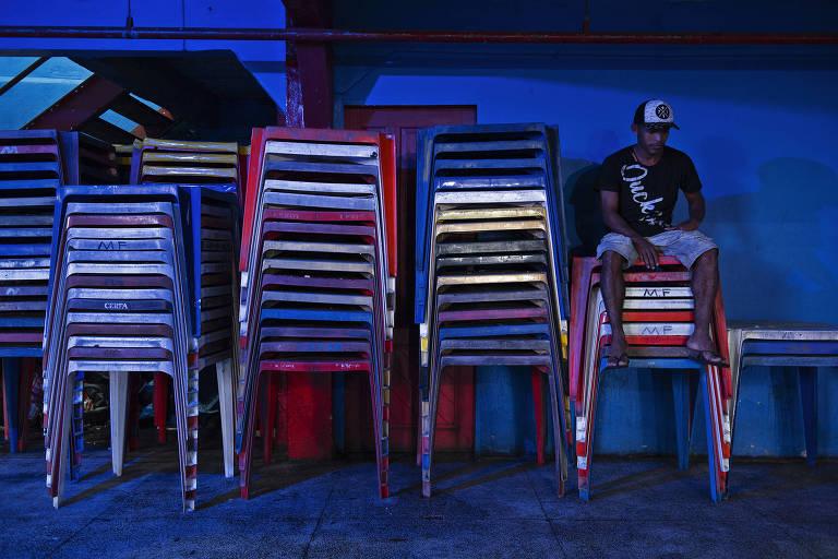 pessoa sentada em mesas coloridas à noite