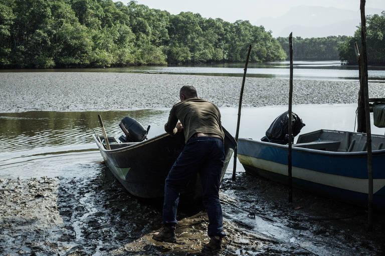 O caiçara Ilson Prado arrasta seu barco para atravessar o rio da Barra do Una (Jureia, SP). Ilson trabalhava na Fundação Florestal e foi, recentemente, demitido