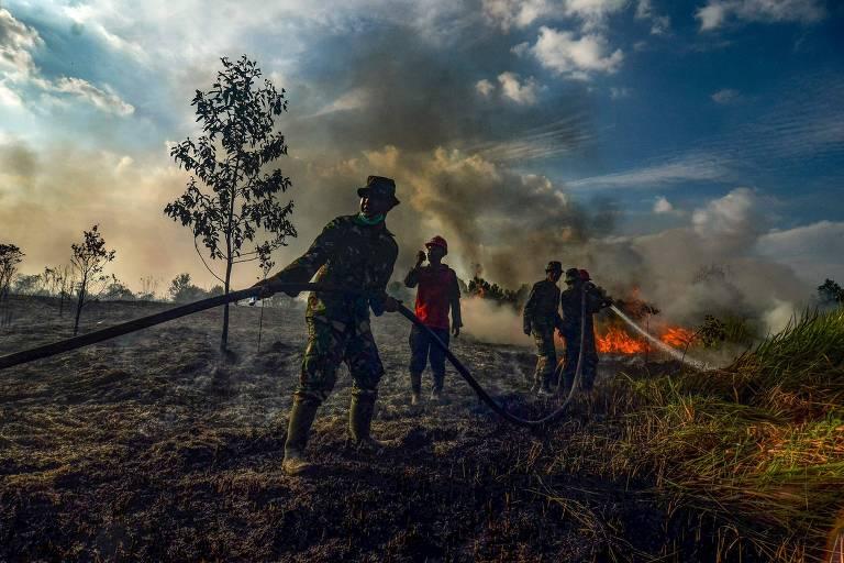 Oficiais da força-tarefa de incêndios florestais e terrestres tentam apagar um incêndio com canos de água em uma plantação de óleo de palma em Pekanbaru, na província de Riau,