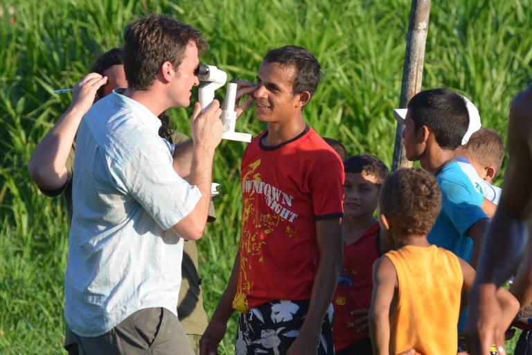Oftalmologistas voluntários do projeto examinam pacientes ao ar livre no interior amazônico