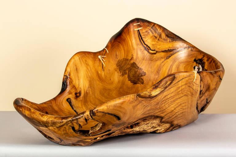 Fruteira de madeira maciça, de formato irregular, com manchas de vários tons