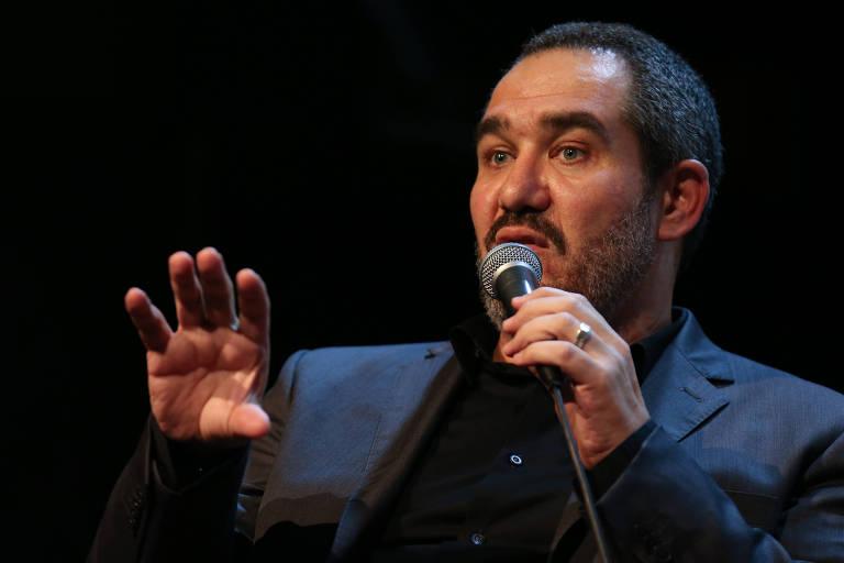 homem em fundo preto fala ao microfone
