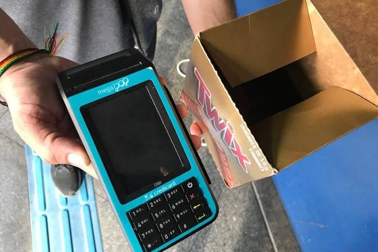 Luiz Rodrigues, 31, vende chocolate no metrô e tem até uma máquina para passar cartão