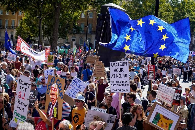 """Manifestantes seguram cartazes onde se lê """"Pare o Golpe"""" e balançam a bandeira azul da União Europeia."""