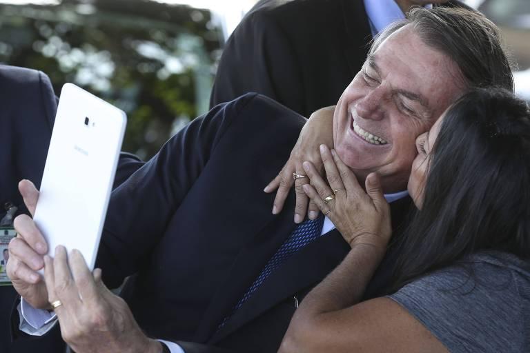 O presidente Jair Bolsonaro segura um celular e sorri para fazer uma selfie ao lado de uma apoiadora, que o beija no rosto