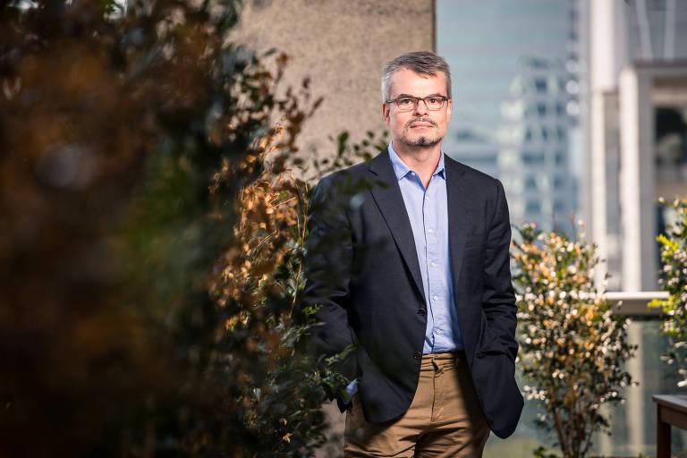 O economista está de pé, em frente a plantas na sacada de seu escritório