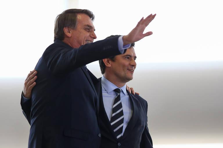 De pé, o presidente Bolsonaro e o ministro Moro sorriem e acenam durante evento no Planalto