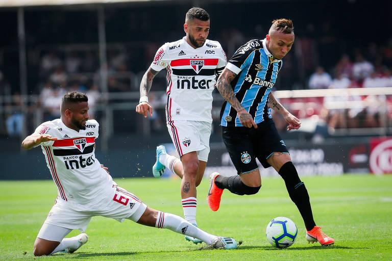 Os são-paulinos Reinaldo (à esq.) e Daniel Alves tentam desarmar o gremista Everton Cebolinha
