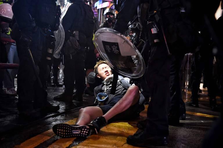 Um adolescente está no chão, aos  pés dos policiais. Ele tem o semblante assustado e sua boca está aberta, como se gritasse