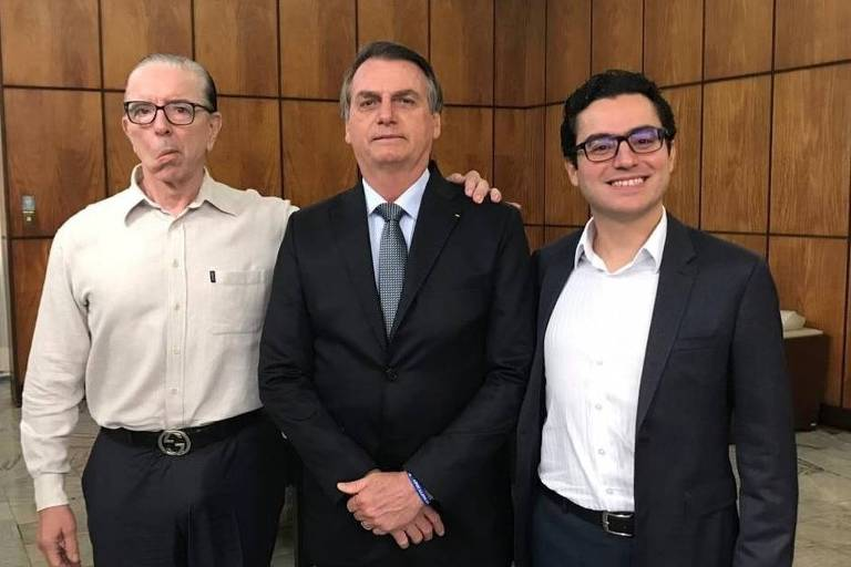 Bolsonaro aparece ao centro, de terno, com as mãos cruzadas em frente ao corpo. É abraçado pelos médicos. O doutor Echenique sorri