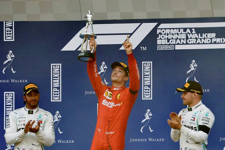 O piloto da Ferrari Charles Leclerc celebra a vitória entre o segundo colocado, Lewis Hamilton (à esq.), e o terceiro, Valtteri Bottas