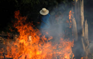 A man works in a burning tract of Amazon jungle as it is being cleared by loggers and farmers in Iranduba