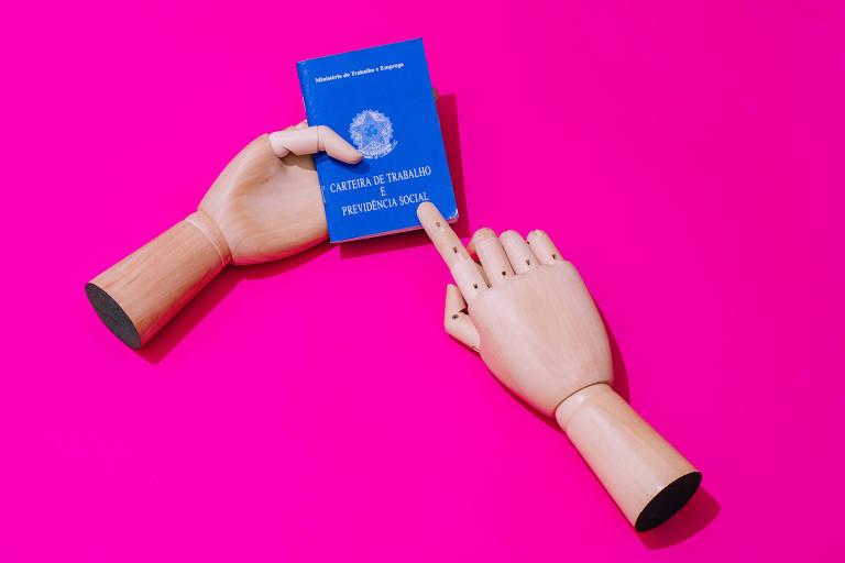 Mãos seguram carteira de trabalho azul sobre fundo rosa shock.