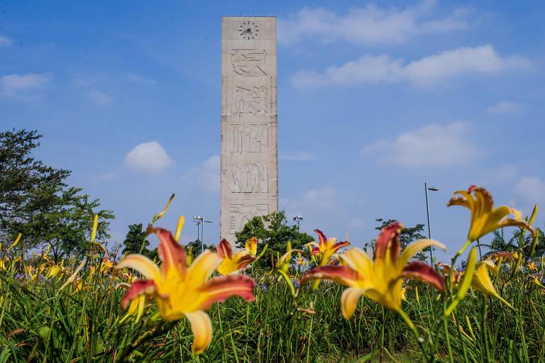 Relógio de concreto em meio a praça com flores