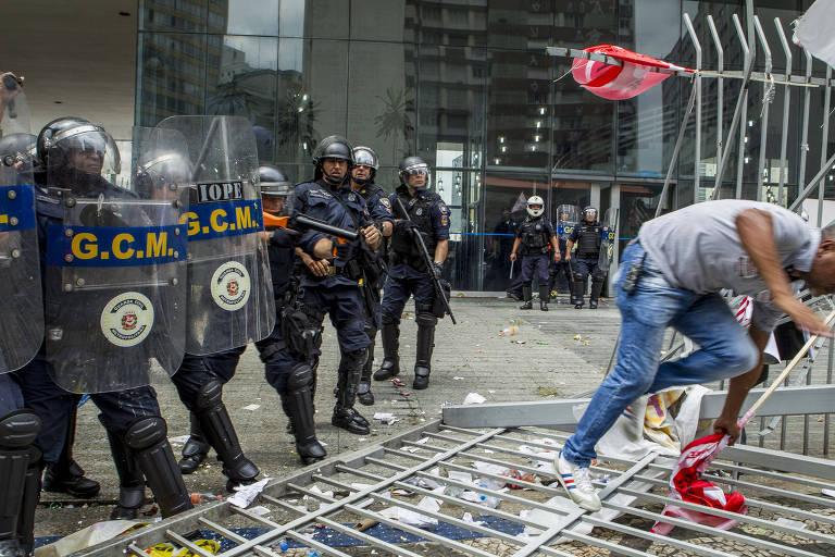 Guardas municipais à esquerda, com escudo protetor, enquanto homem corre, à direita, em cima de portão caído.