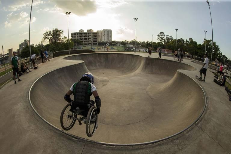Rapaz em uma cadeira de rodas, usando capacete, faz manobra em uma pista de skate