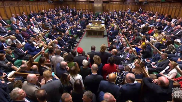 parlamento britânico lotado, no meio, parlamentares aguardam em pé
