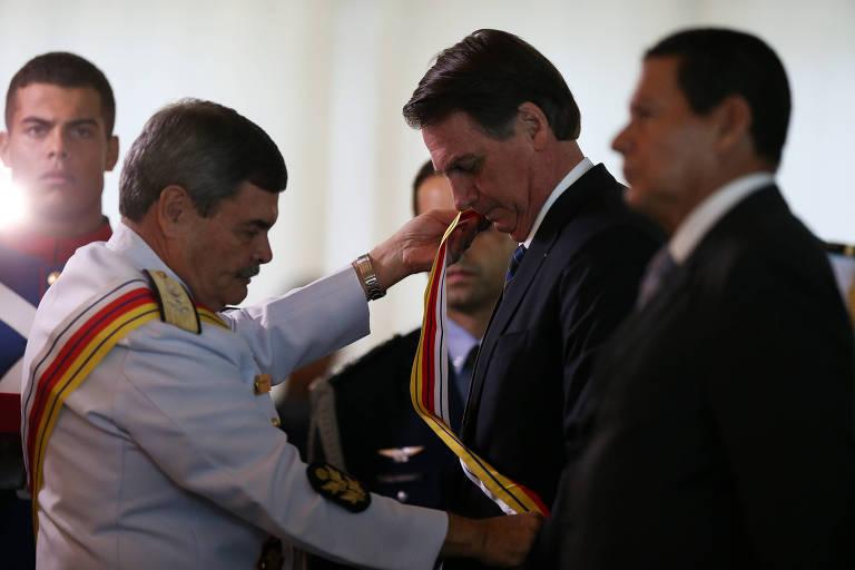 O presidente do STM, Marcus Vinicius Oliveira dos Santos, coloca faixa em Jair Bolsonaro em cerimônia de comemoração ao aniversário da Justiça Militar da União; vice Mourão ao lado