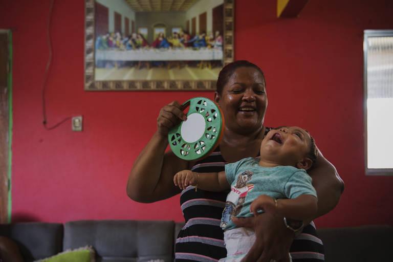 Valéria Gomes Ribeiro estimula o menino João Lucas da Silva Soares, que nasceu com microcefalia, em sua casa na região metropolitana de Recife