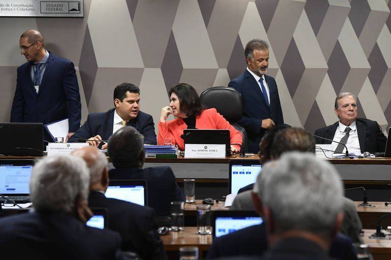A senadora Simone Tebet (MDB-MS), de jaqueta laranja, ao centro, conversa com Davi Alcolumbre (DEM-AP), presidente do Senado, à esquerda; à direita, o senador Tasso Jereissati (PSDB-CE), de terno, olha para o lado esquerdo; ele é relator da reforma da Previdência