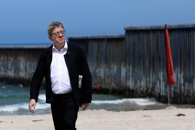 Jean-Luc Melenchon caminha em praia com muro que separa a fronteira ao fundo