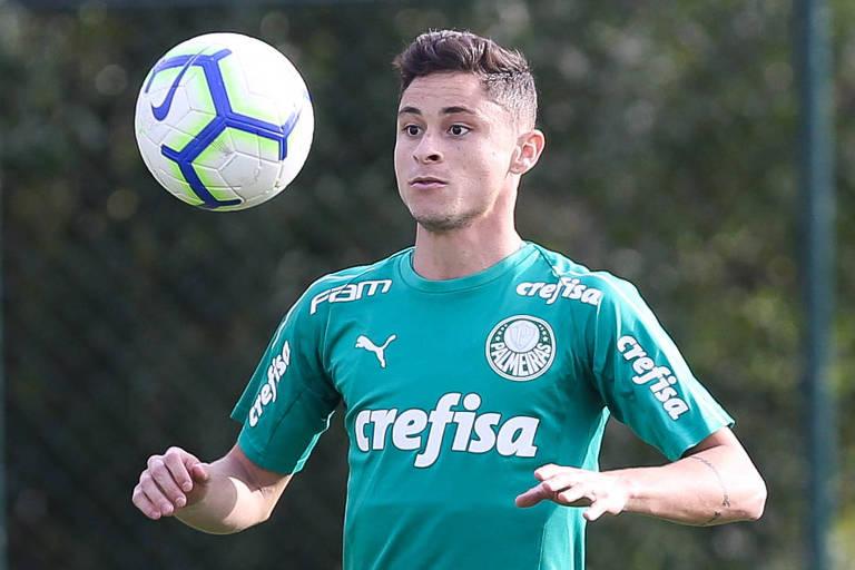 Jogador de camisa verde olha para a bola