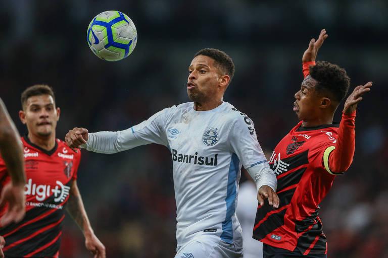 Centroavante gremista André tenta se livrar da marcação de Wellington, do Furacão, no duelo semifinal da Copa do Brasil