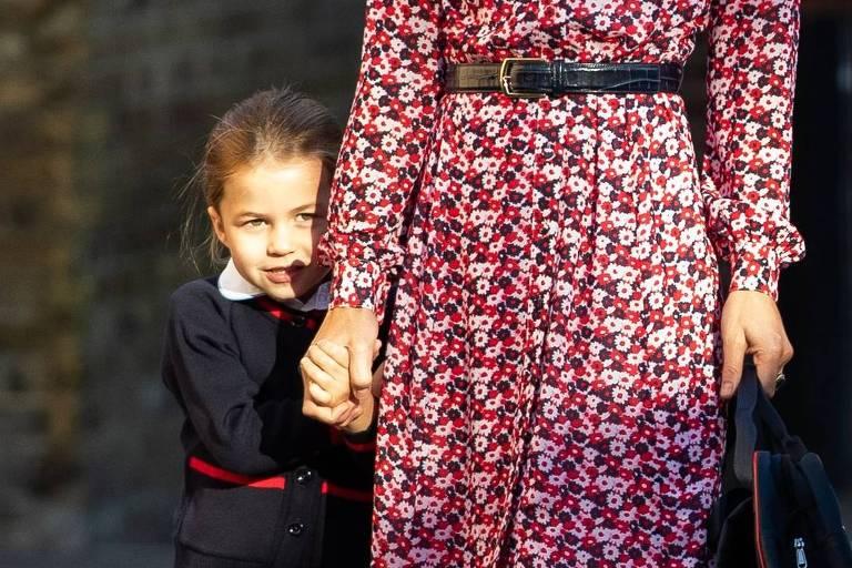 Princesa Charlotte se esconde atrás da mãe, Kate Middleton, enquanto vai ao seu primeiro dia de aula
