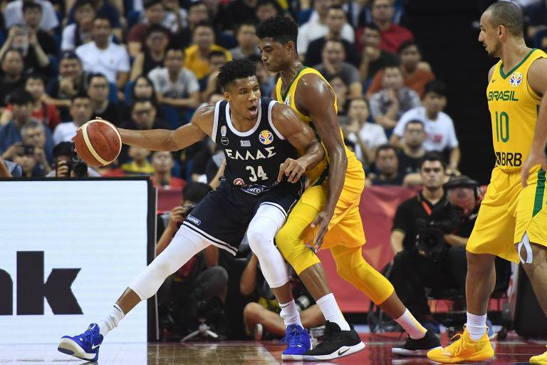 Bruno Caboclo não dá espaço ao grego Giannis Antetokounmpo, enquanto Alex cerca; marcação brasileira parou o melhor jogador da NBA