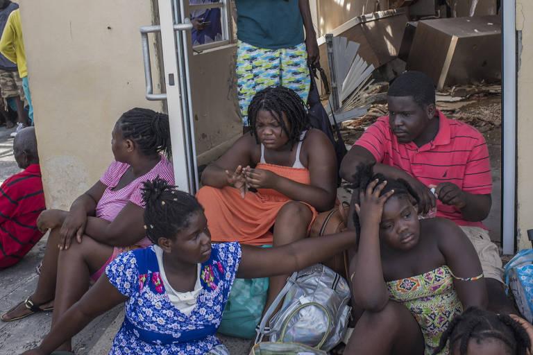 Grupo de haitianos em Treasure Cay, nas Bahamas, onde 95% das casas foram danificadas